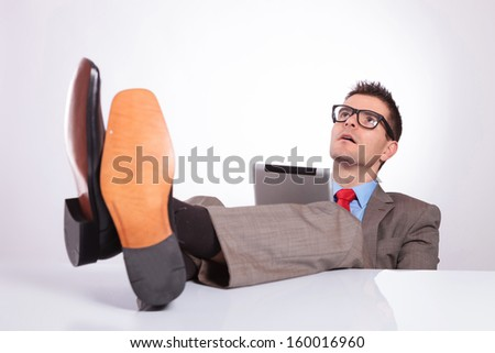 young business man holding his tablet and looking up while holding his feet on his desk. on a gray background - stock photo