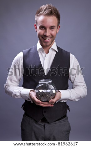 Young business man holding jar with coins  - retirement fund and savings concept - stock photo