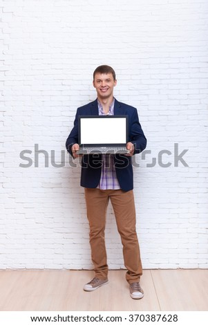 Young Business Man Holding Laptop Screen With Empty Copy Space Full Length Over White Brick Wall - stock photo