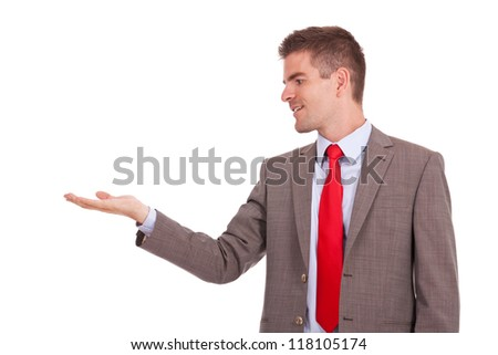 young business man holding something imaginary in his hand and looking at it. isolate on white background