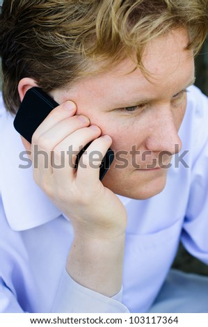 Young Business Man Holds Smart Phone to His Ear - stock photo