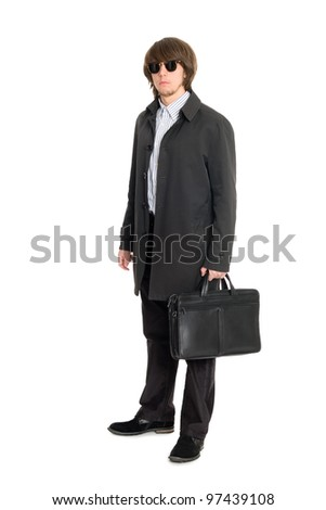 Young business man in a raincoat and sunglasses. - stock photo