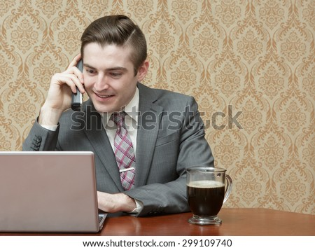 Young business man in a suite and tie with a cup of black coffee on a phone call with a laptop - stock photo