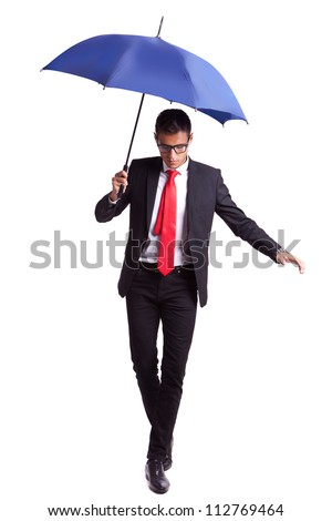 young business man in an equilibrium act, helped by an umbrella, walikng forward - stock photo