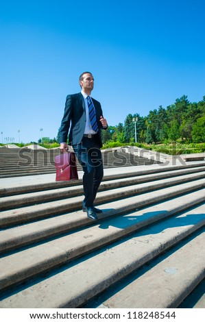 Young business man in dark suit on stairs - stock photo