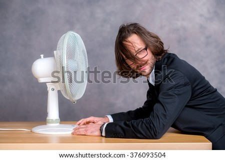 young business man in dark suit sitting in front of fan - stock photo
