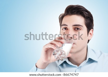 Young business man in drinks a glass of water - stock photo