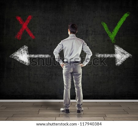 young business man in front of a concrete wall showing two arrows - stock photo