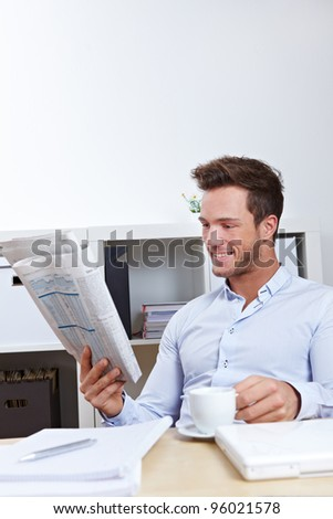Young business man in office reading the appointments section in newspaper