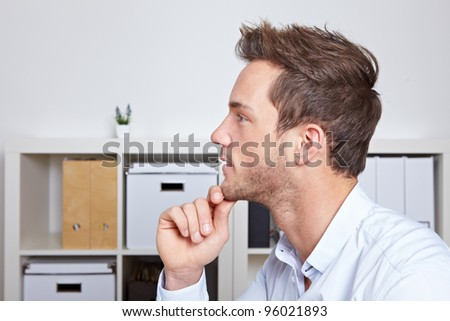 Young business man in profile view with hand on chin in office