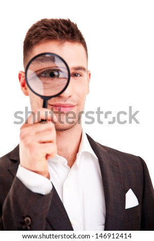 Young business man in suit looking to magnifying glass  - stock photo