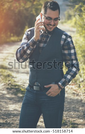 Young business man in the park with phone
