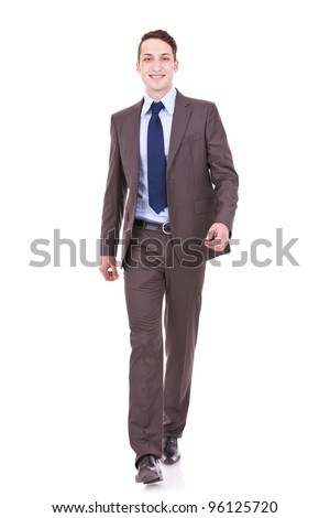 young business man is walking towards the camera. He is smiling and looking to the camera. isolated over white background - stock photo