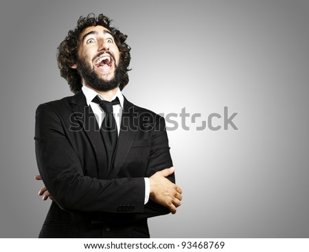 young business man laughing over grey background