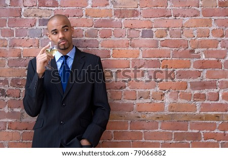 Young business man leaning against the brick wall, thinking and drinking wine.