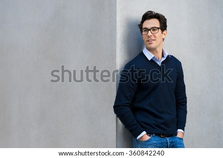 Young business man leaning on a grey wall wearing spectacles. Handsome young man in casual thinking with hands in pocket. Portrait of smiling pensive guy with eyeglasses thinking with grey copyspace.  - stock photo