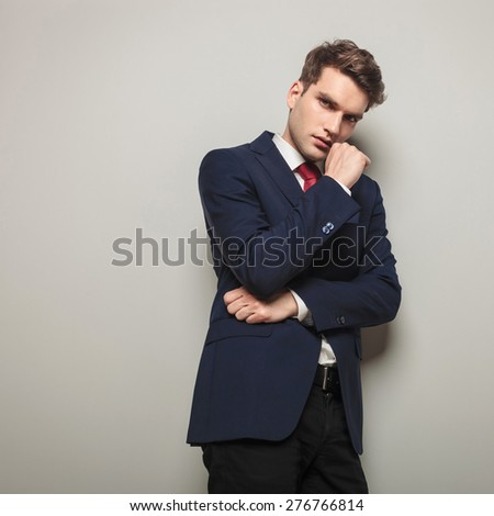 Young business man leaning on a grey wall while thinking on something important. - stock photo
