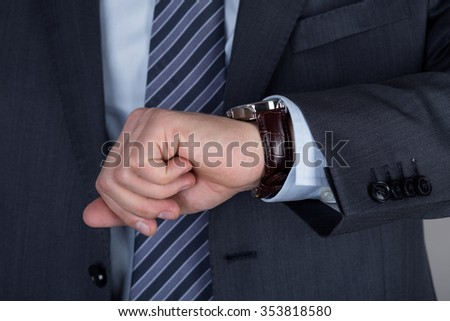 Young business man looking at his wristwatch checking the time. Time management and deadline concept - stock photo