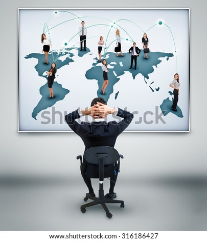 Young business man looking at network world map on wall