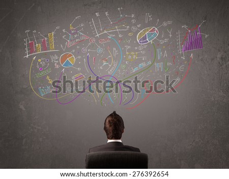 Young business man looking at sketches of graphs and symbols on the wall - stock photo