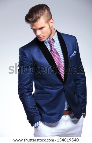 young business man looking down, at his side, away from the camera while holding both hands in his pockets. on a gray background - stock photo