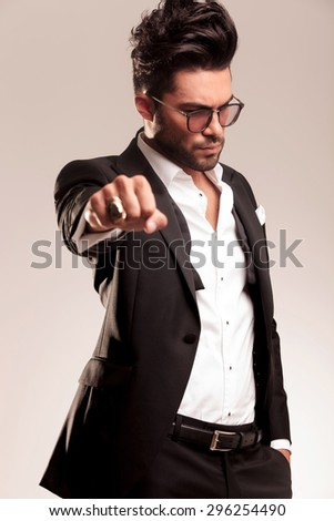 Young business man looking down with one hand in his pocket while showing his golden ring.