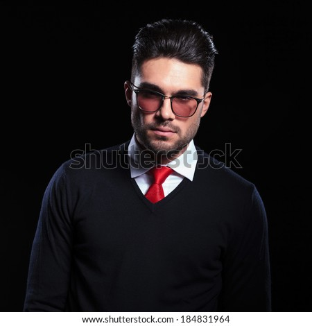 young business man looking into the camera with a serious expression. on a black background - stock photo