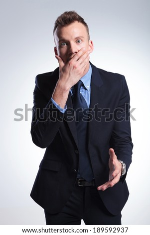 young business man looking shocked with his hand covering his open mouth. on a light gray studio background