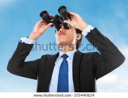 young business man looking through binocular under the blue sky