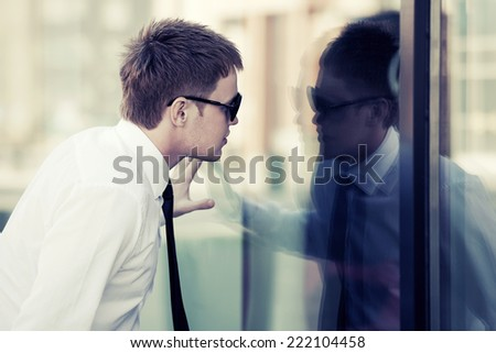 Young business man looking through the office window - stock photo
