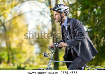 Young business man on a bike hurry to work - stock photo