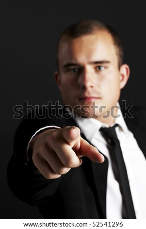 Young business man on black background pointing at you - stock photo