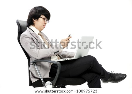 young business man on phone while using computer at workplace