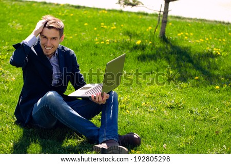 young business man on the grass. fashion style. talking skype. outdoor.smile