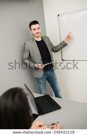 young business man or teacher showing on white board - stock photo