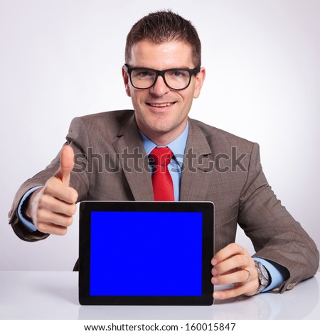 young business man presenting a tablet with a blue screen while showing the thumb up gesture and smiling for the camera. on a gray background