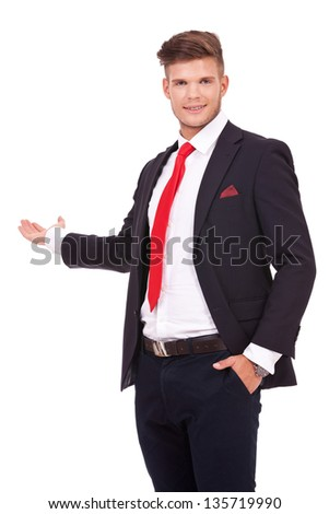 young business man presenting something in his back while holding a hand in his pocket and smiling to the camera. isolated on white background