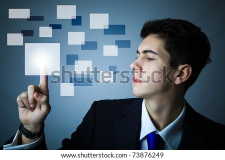 Young business man pressing a digital button - stock photo