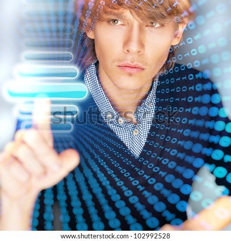 Young business man pressing a touchscreen button while working at his modern office