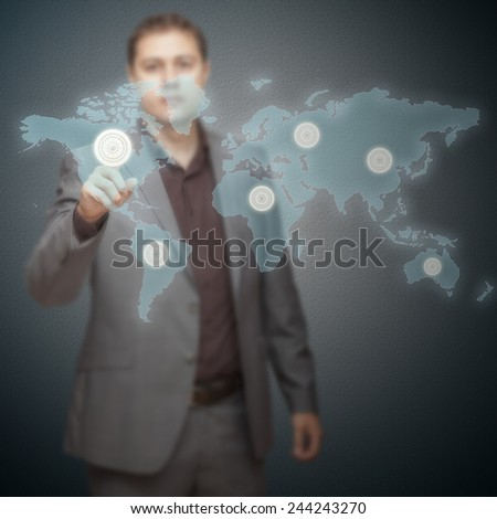 Young business man pressing buttons on world map - stock photo