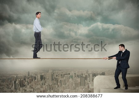 Young business man pulling a tightrope for businessman against balcony overlooking city
