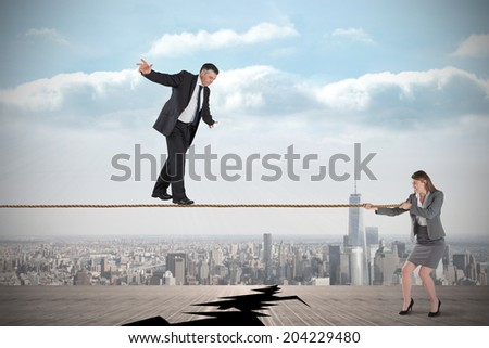 Young business man pulling a tightrope for businesswoman against cracked balcony overlooking city - stock photo