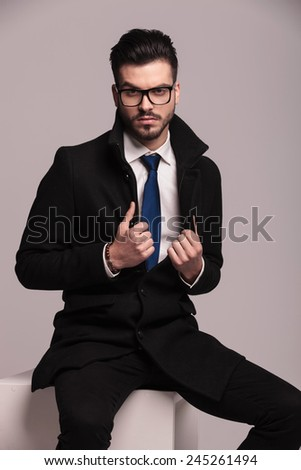 Young business man pulling his collar while sitting on a white modern chair. - stock photo