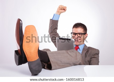 young business man reading something on his tablet and cheering while holding his feet on his desk. on a gray background