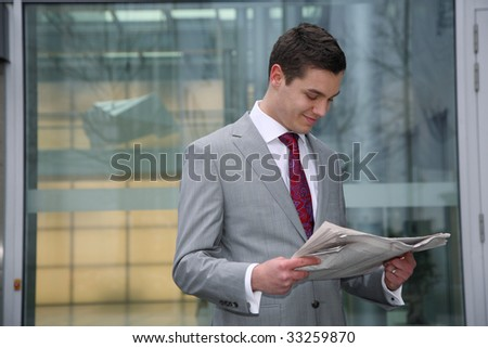 young business man reads newspaper