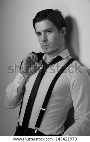 Young business man rests against a white wall - stock photo