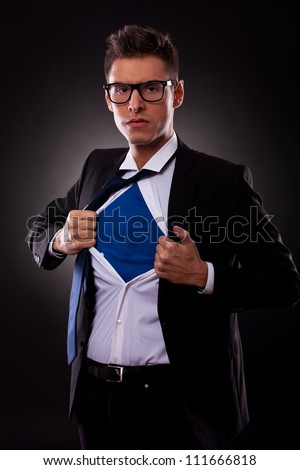 Young business man ripping off his shirt on black background - stock photo