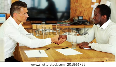 Young business man shaking hands with colleague across the table - stock photo