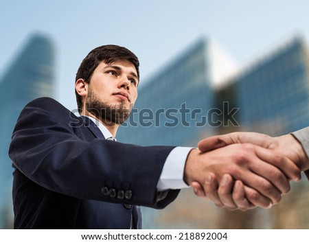 Young business man shaking his hand - stock photo