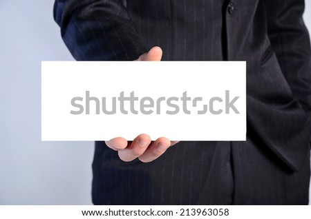 Young business man showing card on blue background